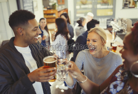 laughing friends toasting beer and wine