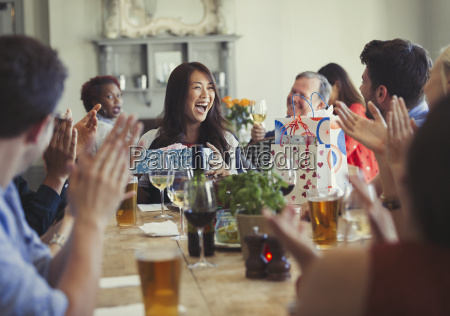 friends clapping for happy woman celebrating