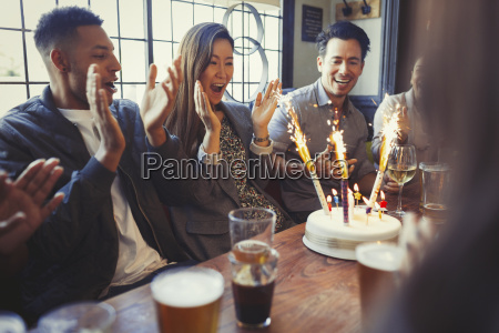 friends cheering for woman celebrating birthday