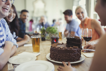 woman serving chocolate birthday cake to