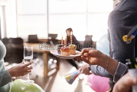 businesswomen surprising coworker with birthday cupcake