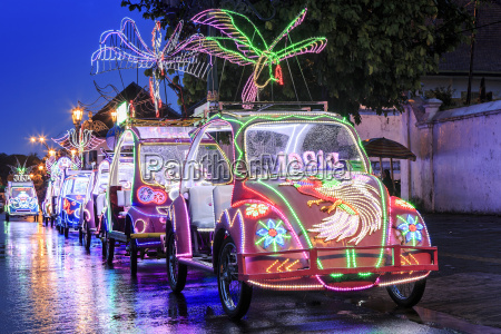 brightly coloured illuminated pedal cars in