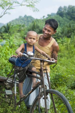 a man balances his little boy