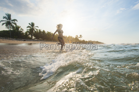 a girl plays in the waves