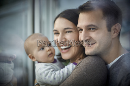smiling happy parents holding baby daughter