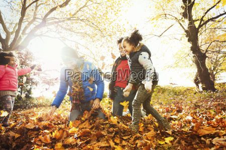 playful young family playing in autumn