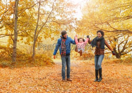 parents swinging daughter in autumn park