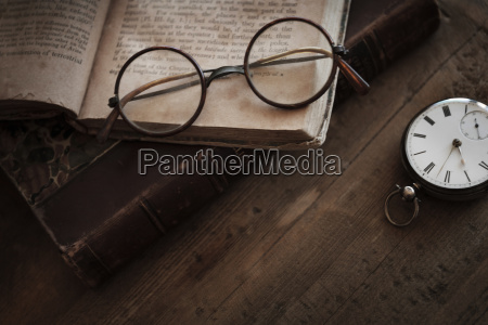 antique book watch and eyeglasses