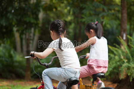 active asian children riding bicycle outdoor