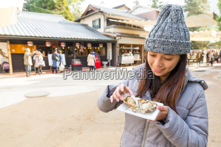 woman enjoy famous oyster in itsukushima