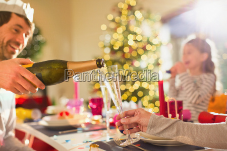 husband pouring champagne for wife at