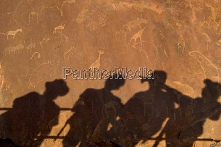 tourist shadows on rock art engravings