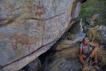 a man looking at rock paintings