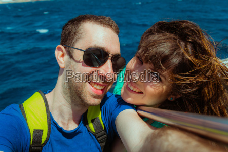 happy couple sailing on a boat