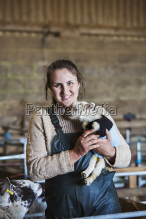 woman standing in a barn holding