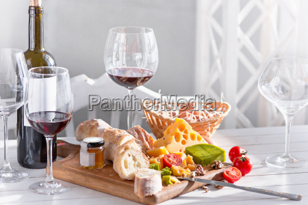 wine baguette and cheese on wooden