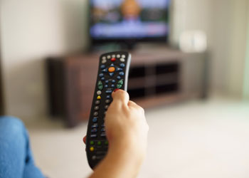 Woman holding remote changing TV channels