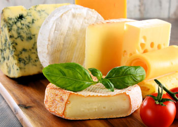 Different types of cheese on wooden board with basil and tomatos