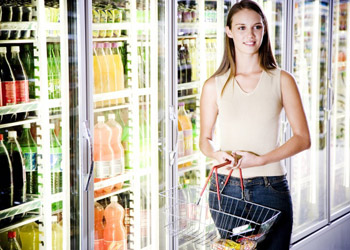 Young woman standing at shopping center next to fridges filled with drinks