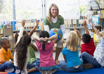 Blonde kindergarten teacher showing preschooler globe