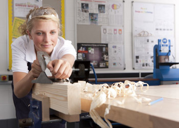 Blond craftswoman shaping wood at workshop