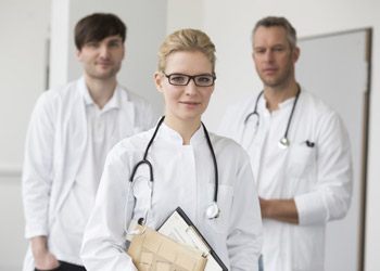 Blond doctor standing with two other doctors
