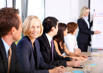 Blond woman sits at desk with business partners attending a meeting