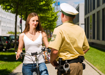 Police man talking to a woman riding a bike on the street