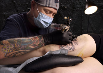 Tattoo artist tattooing someone's leg