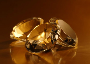 Three luxury shiny diamonds lying on a brown table
