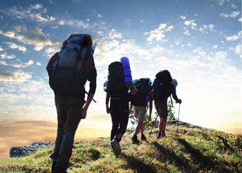 Four wanderer and backpacker hiking up a track by sunrise